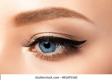Close up view of blue woman eye with beautiful golden shades and black eyeliner makeup. Classic make up. Studio shot