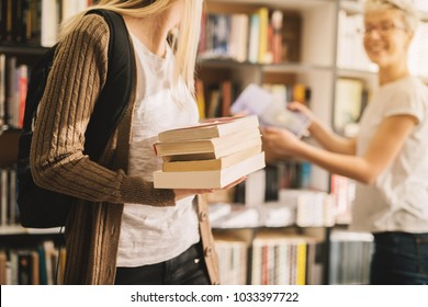 Close view of book stack held by a young high school student girl in the library.