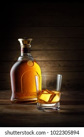 close up view of  bottle and glass of  whiskey  on wooden background