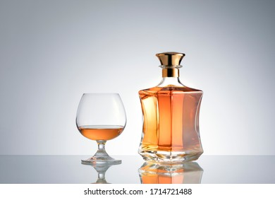 close up view of bottle of whiskey and a glass aside on grey back.