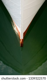 Close up view of the bow of a small white fishing boat afloat in the bay at Palma in Mallorca.