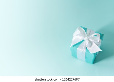 Close view of the box tied with silk ribbon on tiffany blue color pastel background. Gift festive selection.