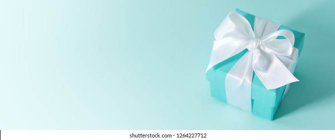Close view of the box tied with silk ribbon on tiffany blue color pastel background. Gift festive selection. long wide banner with copy space