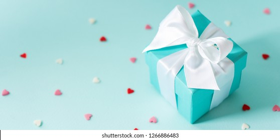 Close view of the box tied with white silk ribbon on tiffany blue color pastel background with tiny hearts. Best gift for girls concepts