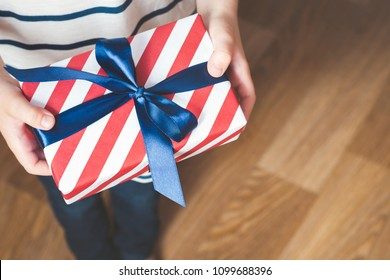 Close up view of boy holding gift box wrapped in stripes paper and tied with blue bow. Father's day background.