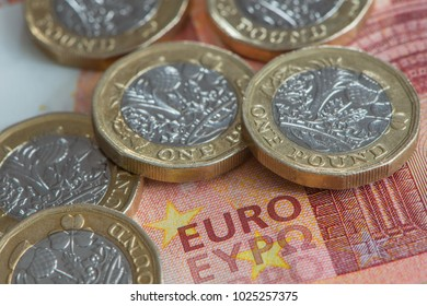 A close up view of British Pound coins on Euro banknote