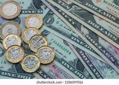 Close up view of British pound coins with various US Dollar notes