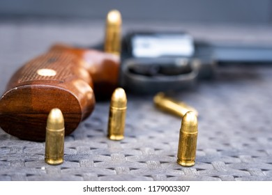 Close up view of bullets and handgun. Shallow depth of field. Revolver out of focus.