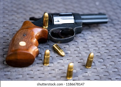 Close up view of bullets and handgun. Shallow depth of field. Revolver in a focus.