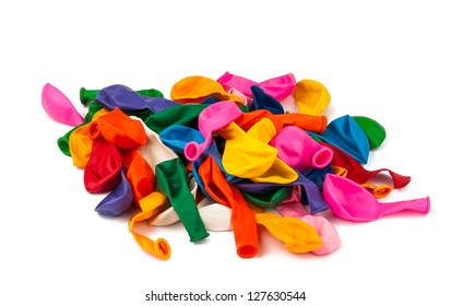 Close view of a bunch of colorful deflated balloons isolated on a white background.