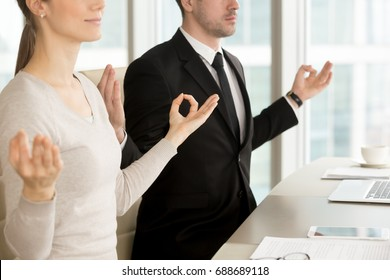 Close up view of business people meditating at desk, practicing pranayama technique to relax at office, holding hands in chin mudra gesture, corporate yoga, stress management for workspace wellness