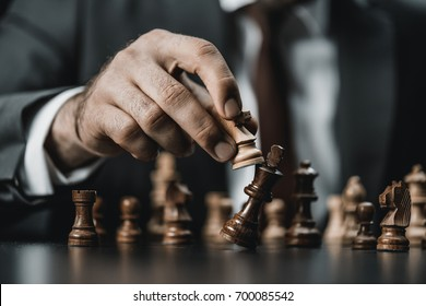 close up view of businessman holding chess figure in hand