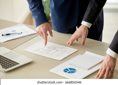 Close up view of businessmen discussing building plan, property value estimation, analyzing real estate market with infographic statistics, house evaluation, construction investment, home appraisal