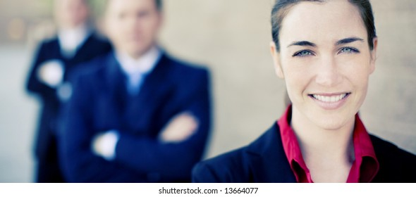 close view of businesswoman and businessmen standing in a row smiling