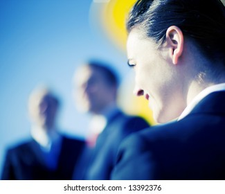 close view of businesswoman looking forward with businessmen standing in front