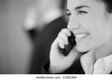 close view of businesswoman smiling with cellphone next to face