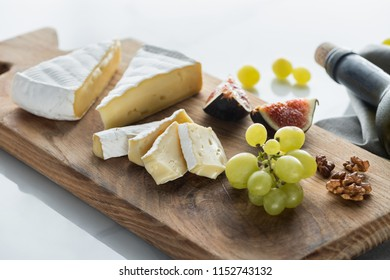 close up view of camembert cheese, grape and fig pieces on cutting board on white tabletop