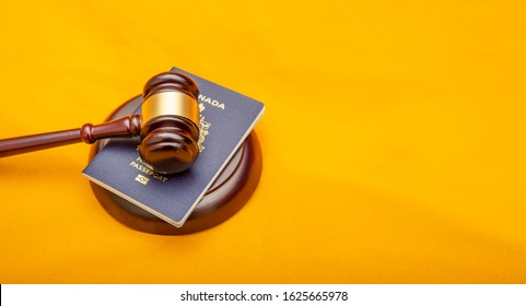 Close up view of canadian passport and Judge gavel, immigration law.