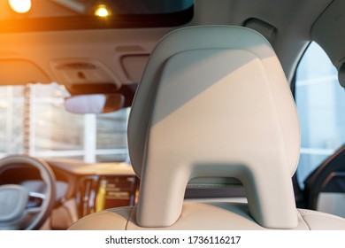 A close up view of car seat headrest. White leather interior of a new modern car, evening sun coming through the window.
