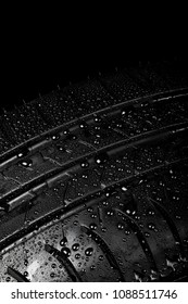 Close up view of a car tyre isolated on a black background with water drops