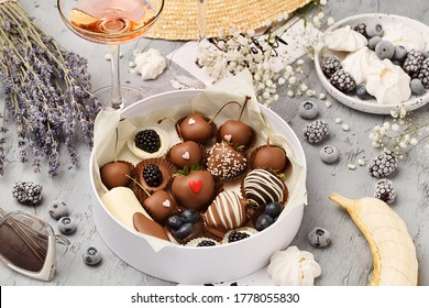 Close up view of cardboard gift box with chocolate covered berries over gray concrete background with straw hat, sunglasses, lavender bouquet, champagne glasses and flowers