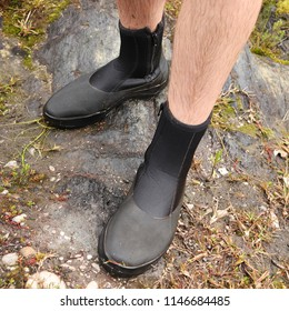 A close up view of a Caucasian man wearing black wading boots.