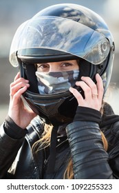 Close up view at Caucasian woman motorcyclist wearing crash black helmet on her head