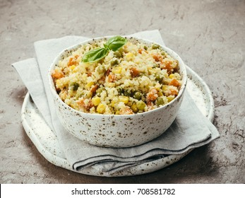 Close up view of cauliflower rice with vegetables. Organic paleo Cauliflower Rice with corn, green peas and carrots on brown concrete background. Copy space.