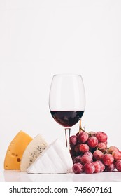 close up view of cheese, glass of red wine and grapes isolated on white