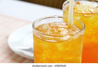 Close view of chilled iced lemon tea served in glass with straw