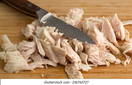 Close view of chopped turkey on a wood cutting board with a knife.