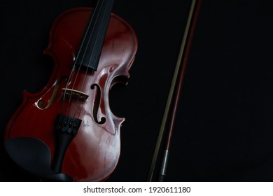 Close view of a classical small violin, strings and bridge over a dark black blanket background