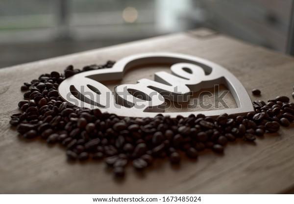 """Nahaufnahme von Kaffeebohnen in weißer Herzform mit """"Liebestext"""". Selektiver Fokus. Holztisch.unscharfer Hintergrund."""