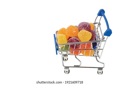 Close up view of colorful marmalade in shopping cart on white background isolated. Unhealthy food concept.