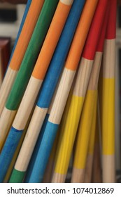 Close up view of colorful wooden sticks. Painted elements in various colors: orange, white, yellow, green, blue and red. Abstract image of vertical mikado pieces with big dimensions. Vintage design.