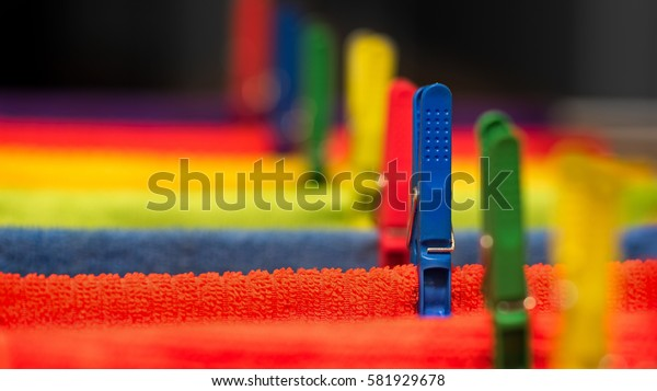Close Up View Of Colourful Bright Towels and Pegs On A Clothesline