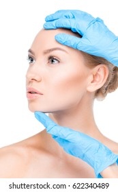 close up view of cosmetologist in latex gloves examining face of female patient