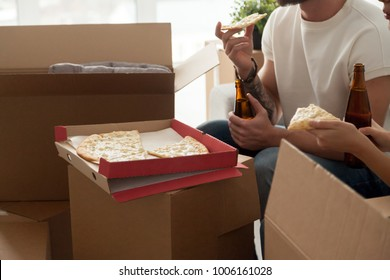 Close up view of couple eating cheese pizza drinking beer celebrating moving day, man and woman having housewarming party together or taking break unpacking boxes in new home, delivery service