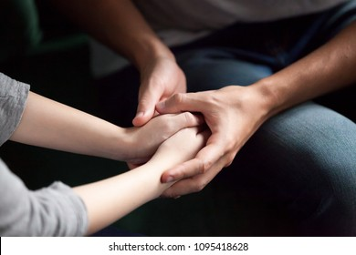 Close up view of couple holding hands, loving caring man supporting comforting woman, giving psychological support, help or protection, understanding in marriage relationships, reconciliation concept