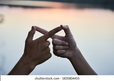 Close up view of couple in love gesturing infinity with fingers. Man and woman making infinity symbol with hands against bright sunshine