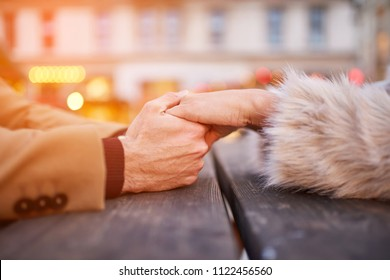 Close view of a couple sitting and holding hands in a christmas market.
