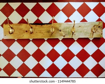 Close up view of crafted vintage re cycled salvaged pine wood clothes rail hanger rail with Art Deco 1930ssolid brass hooks against a background of antique red white Victorian flagstone floor tiles