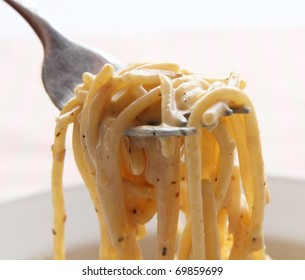 Close view of creamy spaghetti on fork