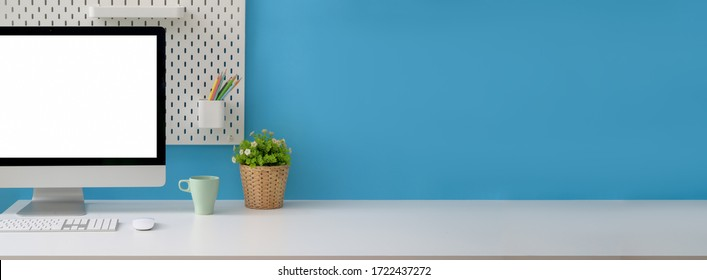 Close up view of creative workspace with blank screen computer, mug, tree pot and copy space on white table with shelf on light blue wall