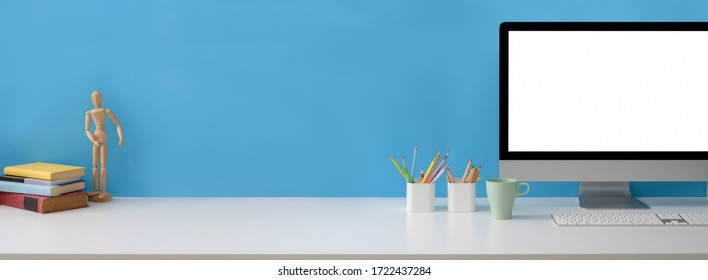 Close up view of creative workspace with blank screen computer, supplies and copy space on white table with light blue wall