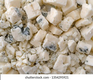 Close view of crumbled blue cheese illuminated with natural lighting.