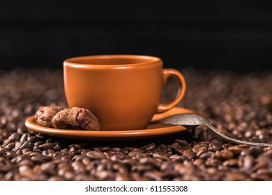 close up view of cup of coffee with cookies on roasted coffee beans