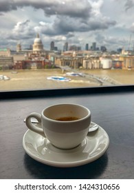 Close up view of cup of coffee on saucer on wooden table, from the Tate Modern coffee shop, London. In background we can glimpse the city skyline: Themes river, Millennium Bridge, Sain Paul Cathedral