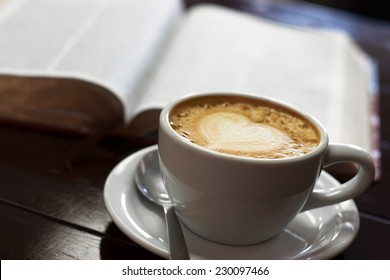 A close up view of a cup of latte with the bible behind it.