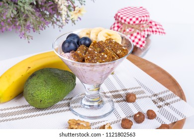 Close up view of cup and raw vegan energy sweets, bars with mix of fruits and nuts. Lifestyle healthy eating concept with breakfast or snack.